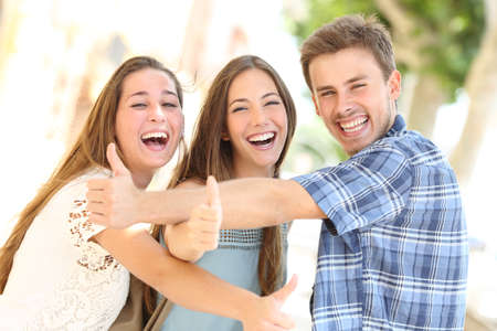 Three happy teenagers laughing with thumbs up looking at you in the street Foto de archivo