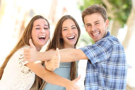 reir: Tres adolescentes felices que ríen con los pulgares arriba mirando a ti en la calle Foto de archivo