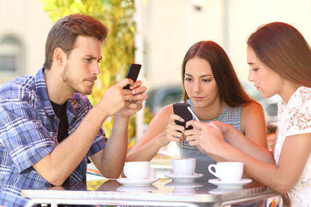 Group of three smart phone addicted friends in a coffee shop terrace everyone with one cellphone 免版税图像