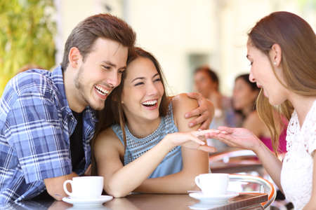 mariage: Couple montrant sa bague de fiançailles à un ami dans un café
