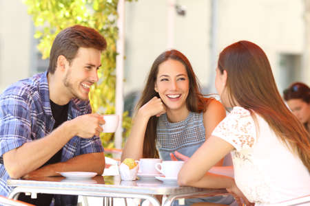 Three happy friends talking and laughing in a coffee shop terrace Stockfoto
