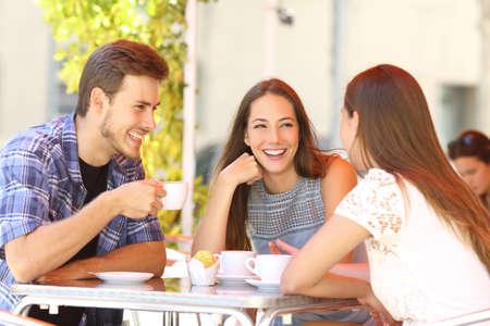 socializando: Tres amigos felices hablando y riendo en una terraza cafetería Foto de archivo