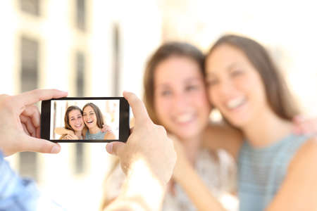cellular: Blurred friends taking photos with a smart phone and showing the photo in the screen on the street