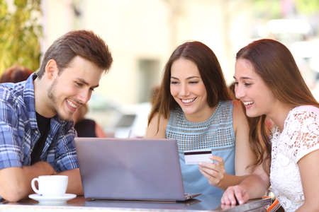 shopping: Tres amigos felices compras en línea con tarjeta de crédito y un ordenador portátil en una cafetería Foto de archivo