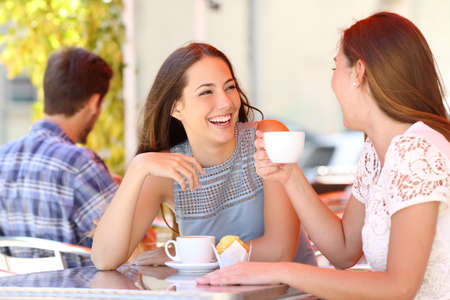 Two friends or sisters talking taking a conversation in a coffee shop terrace looking each other Stock Photo