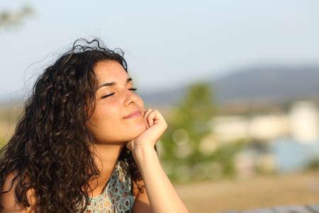 mente: Mujer de relax y disfrutar del sol en un parque de calidez al atardecer