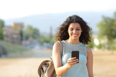 caminando: Vista frontal de una niña de pie feliz y usando un teléfono inteligente en un pueblo
