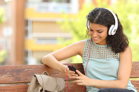 listening device: Woman listening to the music from a smart phone with headphones in a park Stock Photo