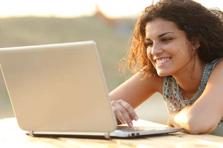Happy woman using a laptop in a park or a home table at sunset