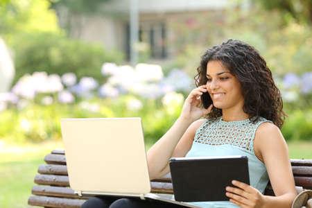 Empresario que trabaja con varios dispositivos que se sientan en un banco en un parque