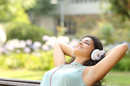 여자는 헤드폰으로 음악을 듣고 공원에서 휴식