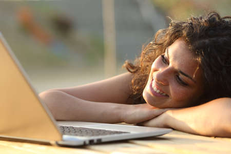 Close up of a woman watching media in a laptop in a park table