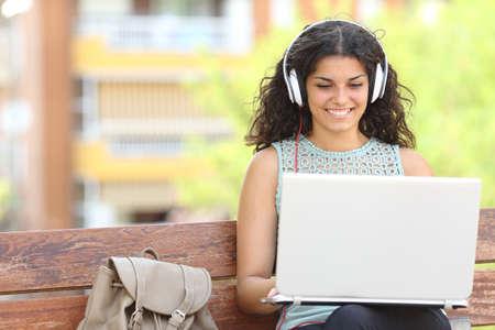 Freelancer werken met een laptop en hoofdtelefoon zittend op een bankje in een park