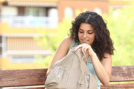 都市公園のベンチに座って彼女の手で何かをお探しの女性のバッグします。