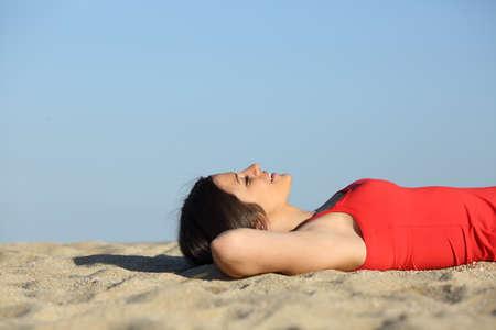 浜辺の砂の上に横たわってリラックスして楽しませる女性の側面図