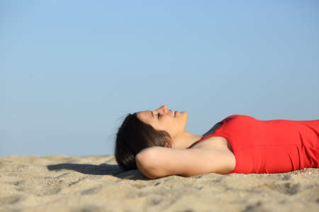 underarms: Side view of a woman resting and relaxing on the beach lying on the sand