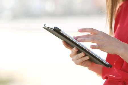 Profile of a woman hands browsing a tablet and touching screen with finger outdoors
