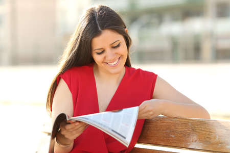 Happy fashion woman reading a magazine in an urban park wearing a red blouse