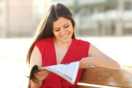 persona leyendo: Moda mujer feliz leyendo una revista en un parque urbano con una blusa roja Foto de archivo