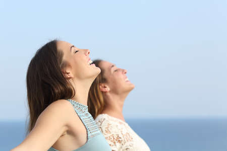Two girls doing breath exercises inhaling fresh air on the beach Foto de archivo
