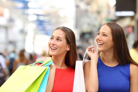 Twee vrienden kopen in een winkelcentrum en houden kleurrijke boodschappentassen Stockfoto