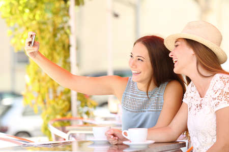 girl posing: Happy tourist friends taking a selfie photo with smartphone in a coffee shop terrace Stock Photo