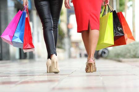 Twee mode vrouwen benen lopen met kleurrijke boodschappentassen in de straat van een stad Stockfoto
