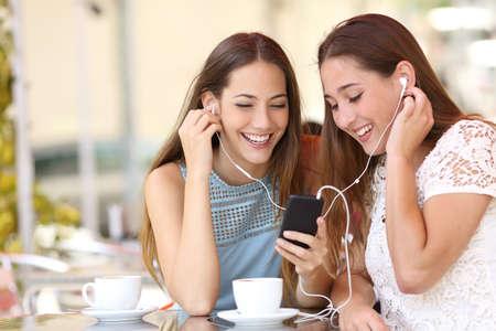 stile di vita: Amici che condividono e ascoltare musica con auricolari e smartphone in un coffee shop
