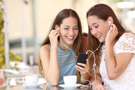 Friends sharing and listening to music with earphones and smartphone in a coffee shop Фото со стока
