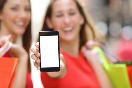 Two joyful shoppers with shopping bags showing a blank smart phone screen in the street Stock Photo
