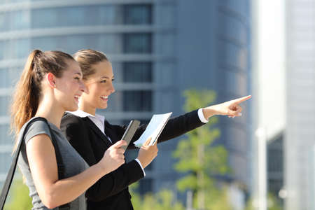 asking: Two businesswomen searching location with mobile phone gps and paper map with office buildings in the background Stock Photo