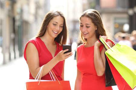 Twee mode kleurrijke shoppers met zakken winkelen met een slimme telefoon in de straat