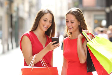 buying online: Two fashion colorful shoppers with bags shopping with a smart phone in the street Stock Photo