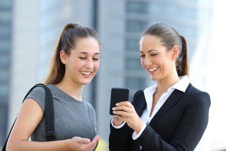 Two businesswomen talking about smart phone in the street with office buildings in the background Stock Photo