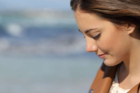 Close-up portret van een melancholische vrouw denken op het strand met de zee op de achtergrond
