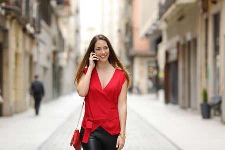 Mode en sexy vrouw lopen en praten over de mobiele telefoon in een stad straat