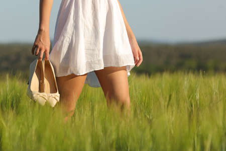 Relaxed woman legs walking in the middle of a field in summer holding high heels