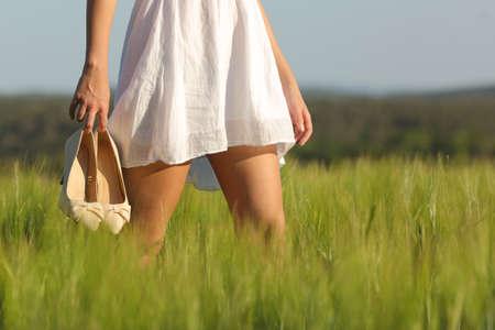 depilacion con cera: Piernas de la mujer Relaxed caminando en medio de un campo en verano la celebración de los tacones altos