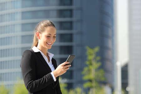 ejecutiva en oficina: Ejecutivo trabaja con un teléfono móvil en la calle con edificios de oficinas en el fondo