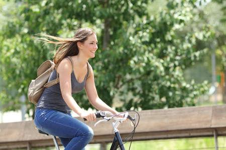 andando en bicicleta: Ciclista de la mujer sana y feliz que monta r�pidamente en una bicicleta en un parque Foto de archivo