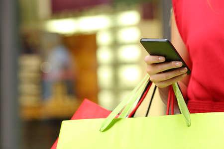 compras: Shopper comercial mano de la mujer con un teléfono inteligente y bolsas de transporte