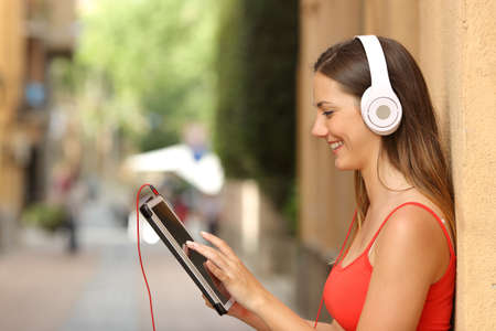 listening device: Happy girl browsing a tablet and listening to the music with headphones leaning on a wall in the street