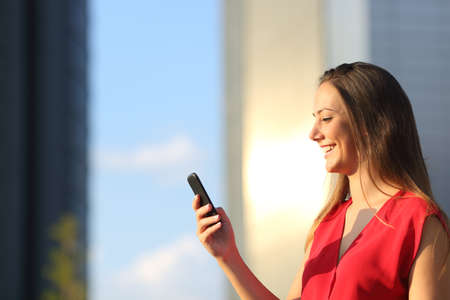Ondernemer zakelijke vrouw met behulp van een slimme telefoon met kantoorgebouwen op de achtergrond