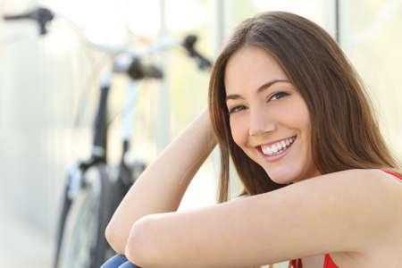 ortodoncia: Retrato de la muchacha con sonrisa perfecta y dientes blancos mirando a la cámara. Concepto de atención dental