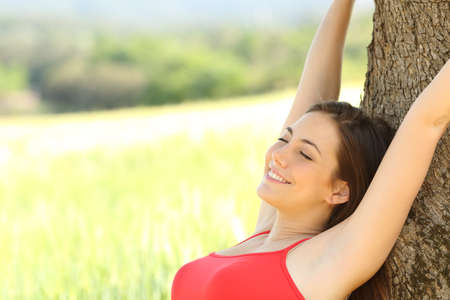 underarm: Happy woman sleeping and resting comfortable in the country under a tree shadow Stock Photo
