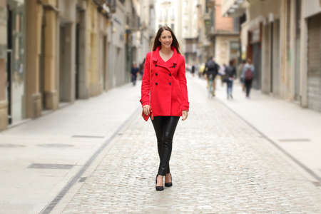 winter fashion: Happy fashion woman in red walking on a city street in winter