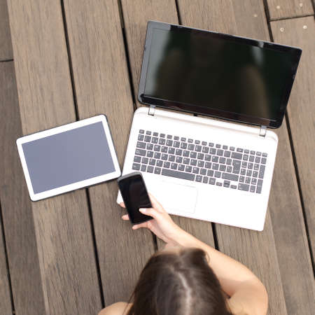 teen: Girl lying in a park searching job in multiple devices showing a blank screens