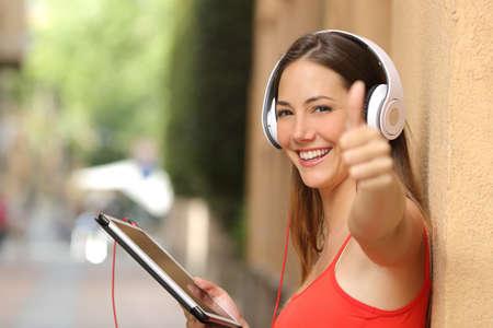 personas escuchando: Feliz niña con una camisa roja con pulgares arriba usando una tableta y escuchar música con auriculares Foto de archivo