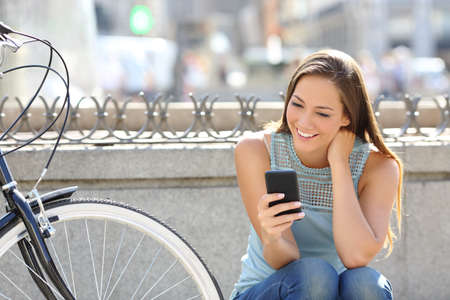 lady with phone: Happy girl watching media in a smart phone sitting in the street beside her bicycle
