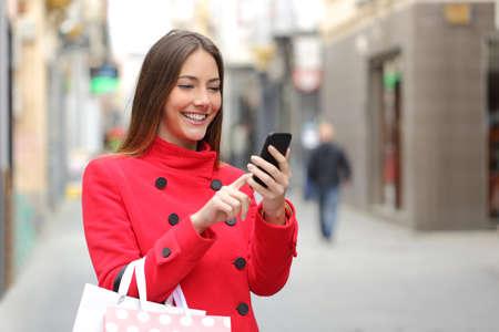 Shopper vrouw koopt online op de smartphone in de straat Stockfoto